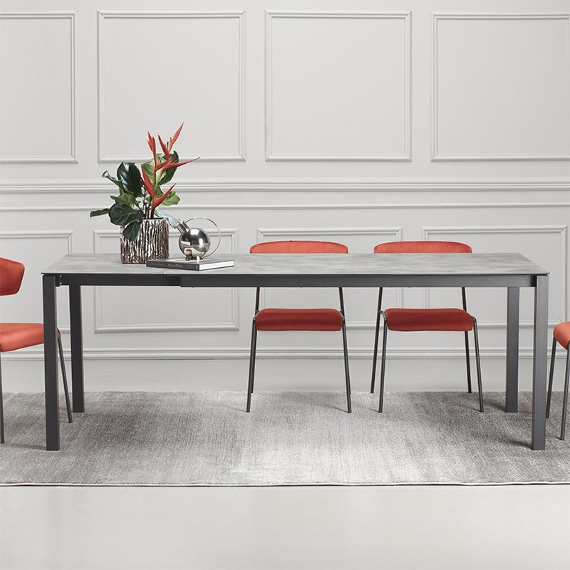 tavolo Pranzo allungabile di scab in metallo antracite con piano in stratificato HPL effetto cemento allungato ambientato